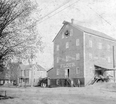 "Flour mill known as the ""Red Mill"". The Corydon Steam Mill Company was built in 1834, and was powered by steam not a water wheel. It was a frame building of 4 stories and an attic. It was located on the SE corner of Chestnut and Mulberry Streets and was in operation for about 90 years. Eventually L.A. Reasor, who lived next door bought the old mill, tore it down and built a large garage and filling station. This information was taken from a book, ""The Streets of Corydon"" by the late Fred Griffin."